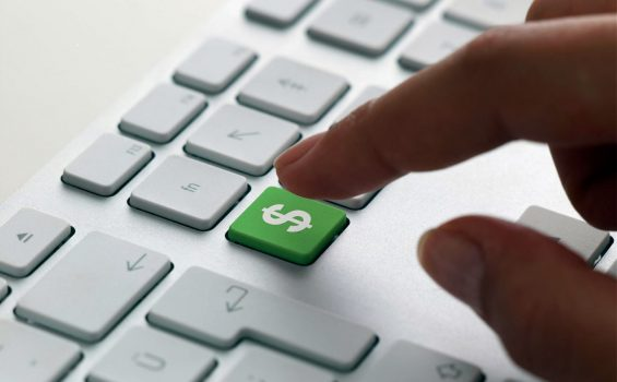Hand of woman using a keyboard with a green dollar sign key