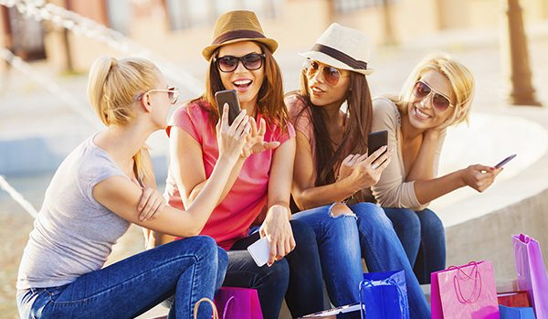 Group of Young Women with Shopping Bags and Smartphones