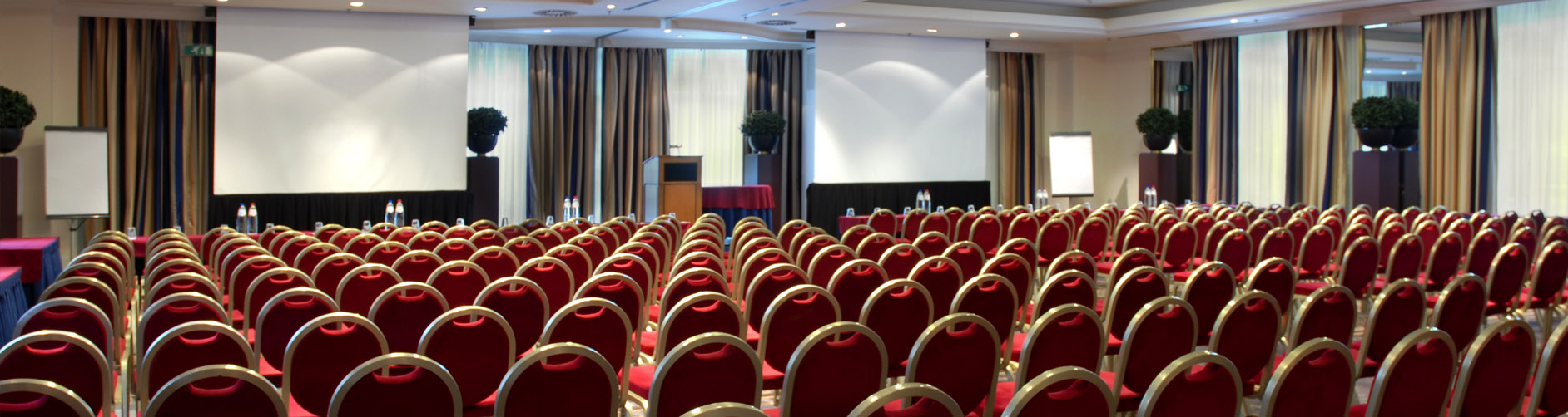 Large Conference Room with Projector Screens and Rows of Chairs