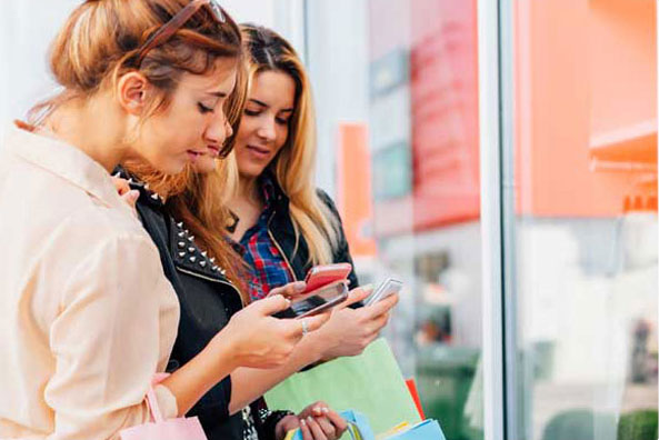 Young Female Shoppers using smartphones and retail WiFi to access coupons