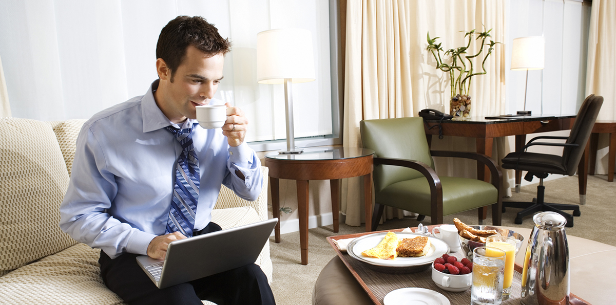 Businessman sips coffee while on his laptop in a hotel room with room-service breakfast.