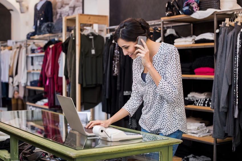 Female Small Business Owner in Clothing Store Using Laptop and Mobile Phone