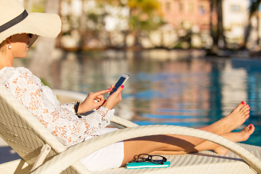 Woman using smartphone to connect to hotel WiFi at the pool
