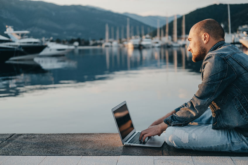 Man sitting on dock using laptop with Marina WiFi