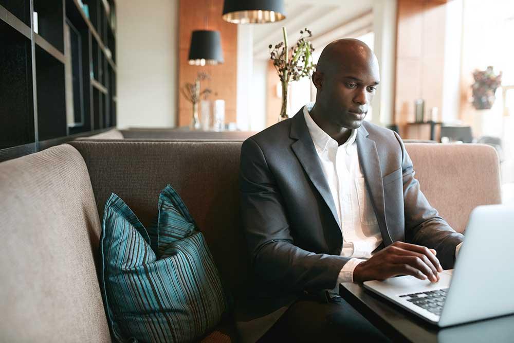 man on laptop in hotel lobby